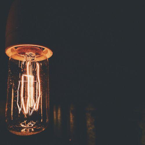Close-Up Of Illuminated Light Bulb In Dark Room