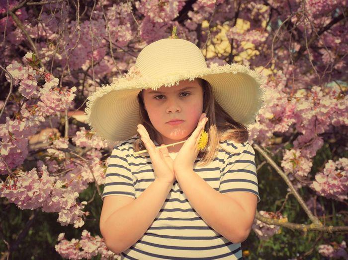 Portrait Of Girl Holding Flower Against Tree