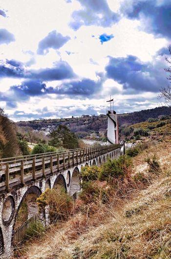 Arch bridge over land against sky