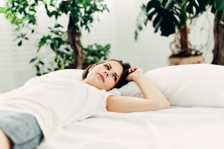 Thoughtful young woman lying in bed at home