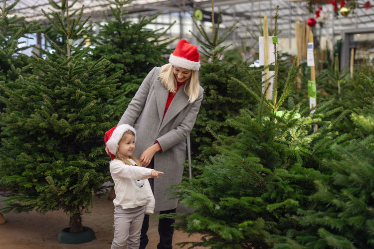 Mother and daughter buying christmas tree