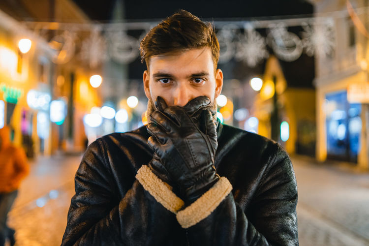 Portrait of young man with hands covering mouth while standing outdoors at night