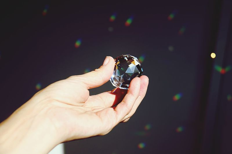 Cropped Hand Crystal Ball Against Black Curtain