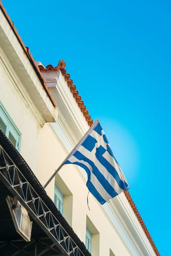 Low angle view of flag waving on building against clear blue sky