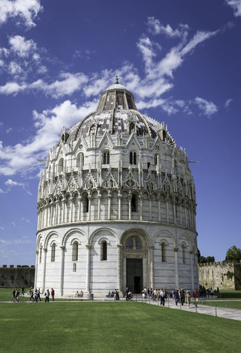 Low angle view of pisa baptistery against cloudy blue sky