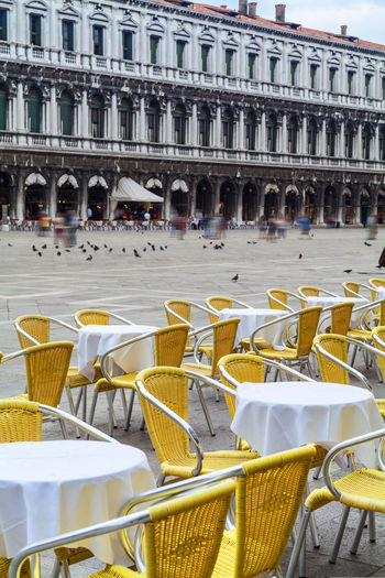 Empty chairs and tables against building at piazza san marco