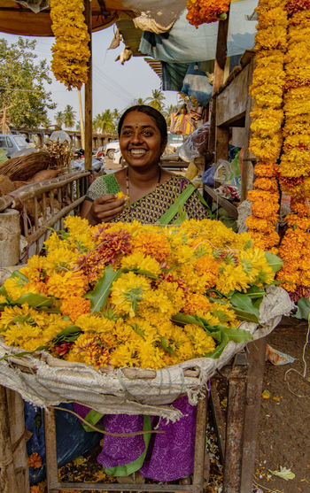 Portrait of a smiling young woman standing at market