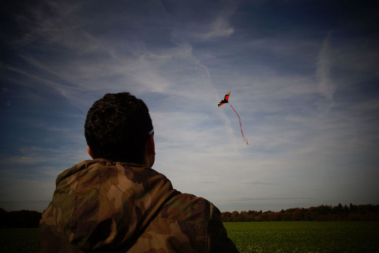 Rear view of army soldier looking at kite on grassy field against sky