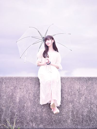Woman standing with umbrella against sky