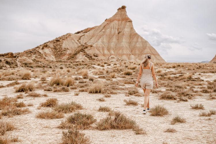 Rear view of woman walking on field against rock mountain