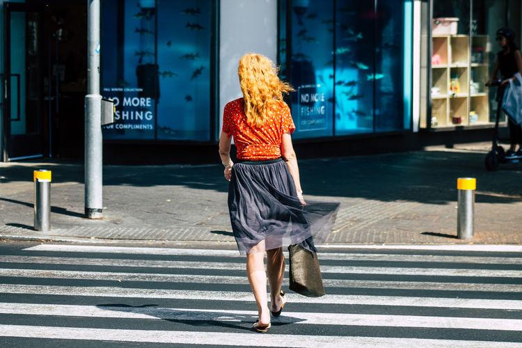 Full length rear view of woman walking on road