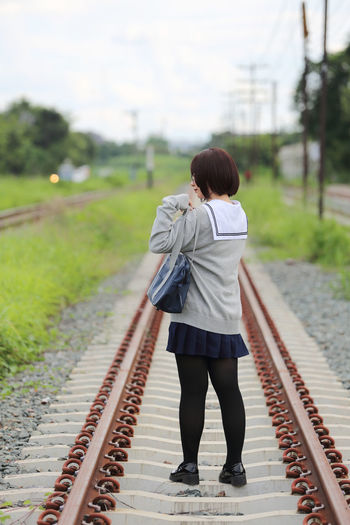 Rear View Of Young Woman In School Uniform On Railroad Track