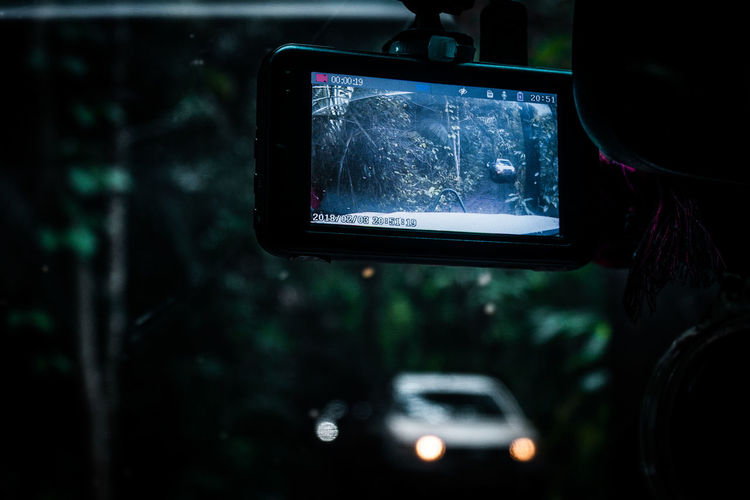 Close-up of reflection of car on side-view mirror