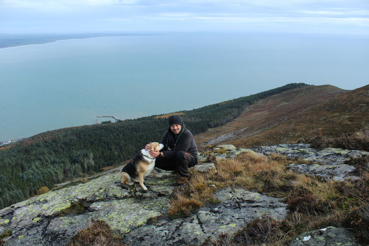 High angle view of man stroking dog at mourne mountains by river