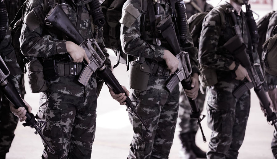 Clos-up of army soldiers with rifle standing outdoors