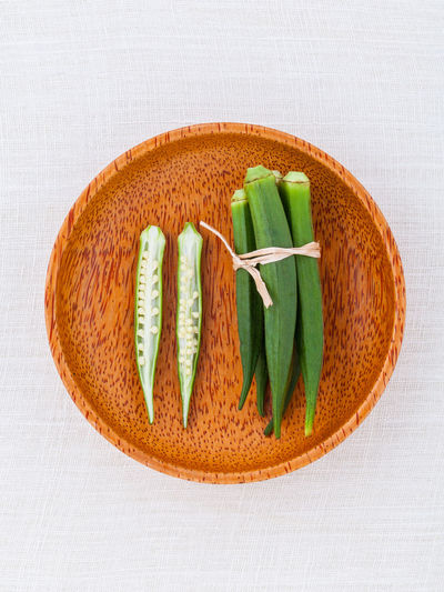 Directly above shot of okras in wooden plate on table