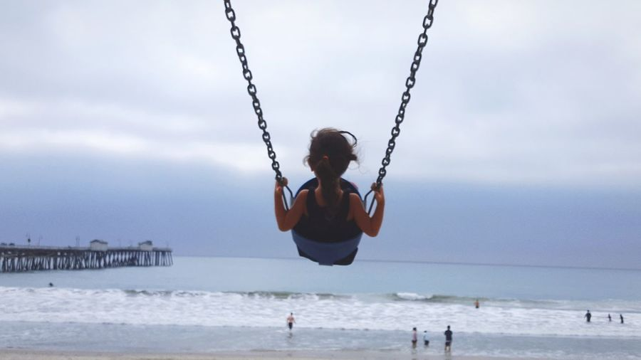 Rear view of girl playing on swing at beach against sky