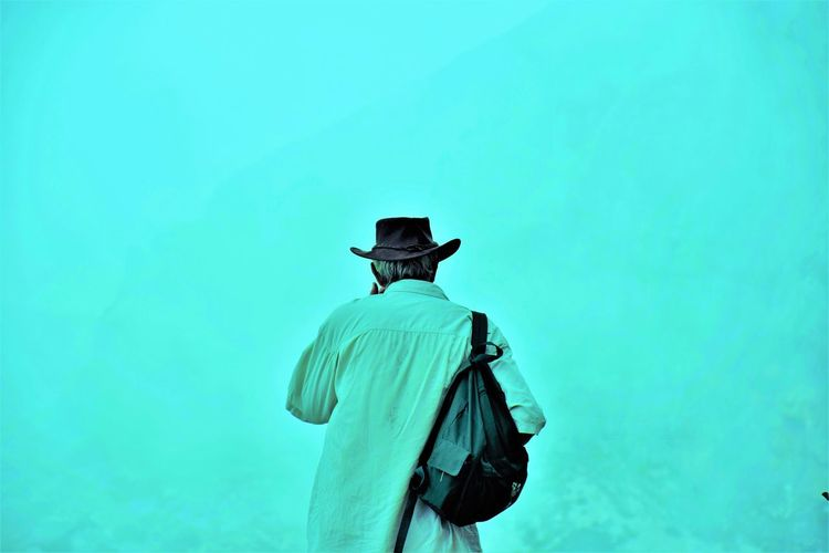 Rear view of man standing against turquoise background