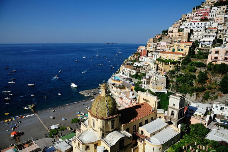 Buildings by sea on cliff against clear sky at positano