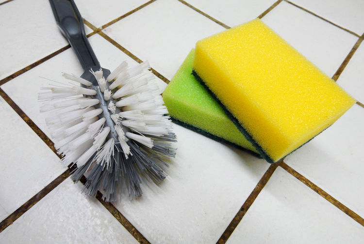 Close-Up Of Brush And Sponge Scrub On Flooring