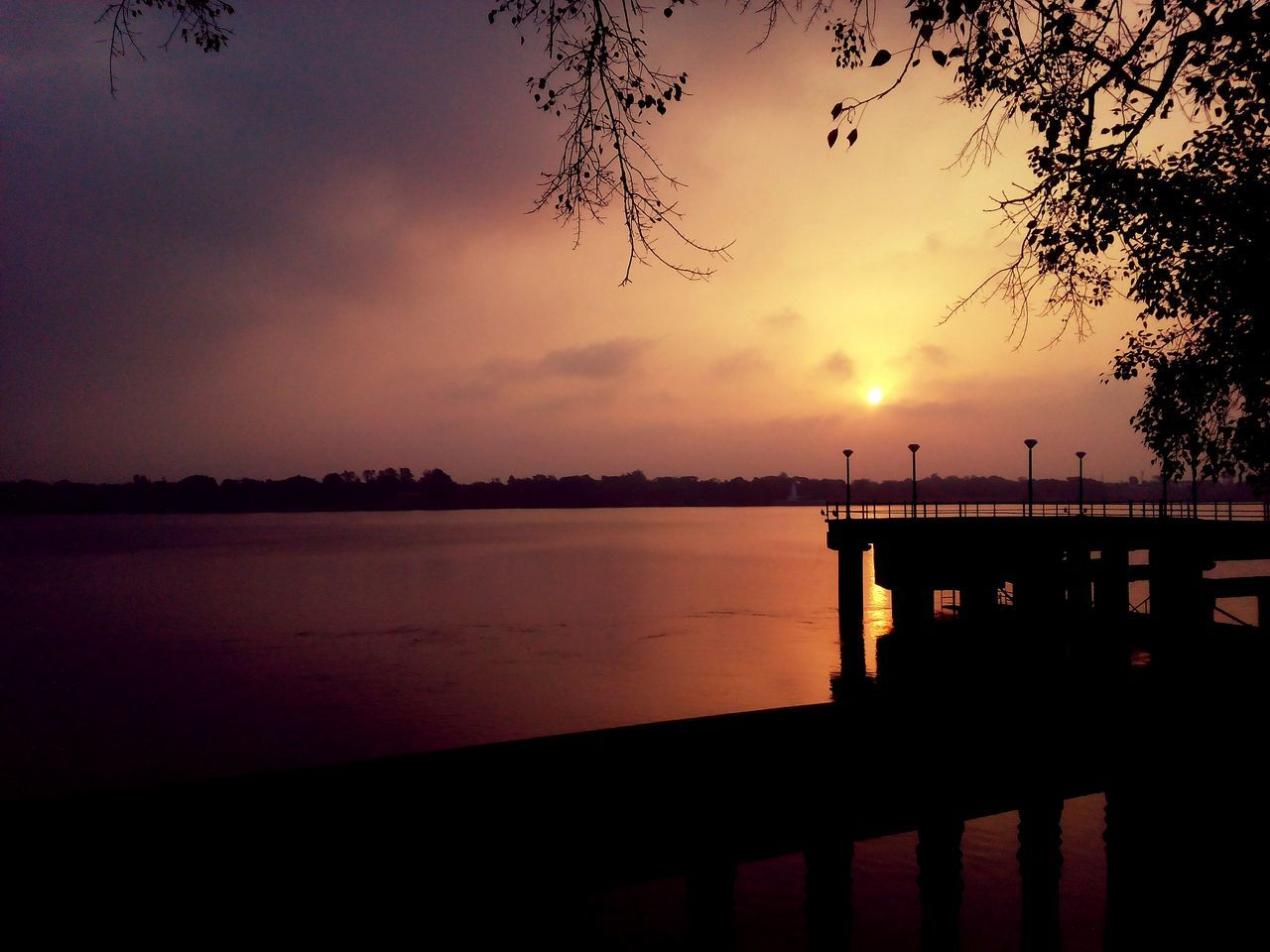 sunset, water, silhouette, sky, tranquil scene, beauty in nature, scenics, sea, pier, nature, tranquility, reflection, idyllic, jetty, outdoors, no people, cloud - sky, travel destinations, built structure, horizon over water, tree, day