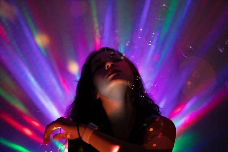 Close-up of woman in illuminated nightclub