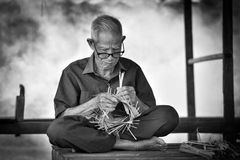 Man making basket while sitting on bench