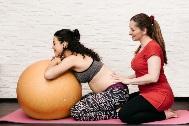 Midwife massaging a pregnant woman while exercising with a fitness ball. 20-30 Years Baby Care Excercising Home Horizontal Motherhood Trainer Antenatal Doula Excercise Fit Fitness Fitness Mat Massage Massaging Midwife Mom To Be Personal Pregnancy Pregnant Prenatal Real People Training Young Women