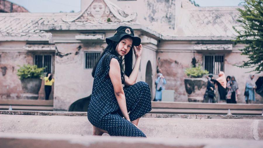 Portrait of woman wearing hat kneeling against built structure