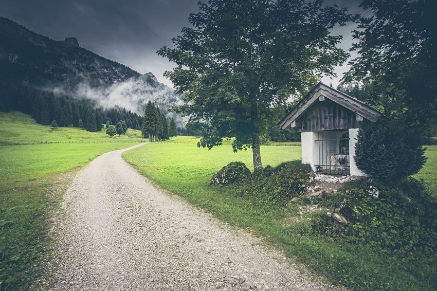 Hiking trail with crucifix at the Alps Alpine Bavaria Catholic Christianity Cross Garmisch Hiking Idyll Marterl Pasture Road Spirituality Alps Bayern Hiking Trail Landscape Mountain Nature The Way Forward Tourism Trail Tranquility Unfiltered Vacation Vintage