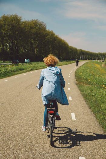 Rear View Of Woman Cycling On Road Against Sky