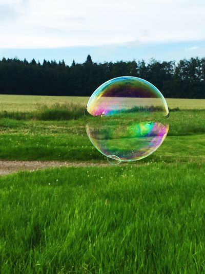 Multi colored bubbles in field against sky