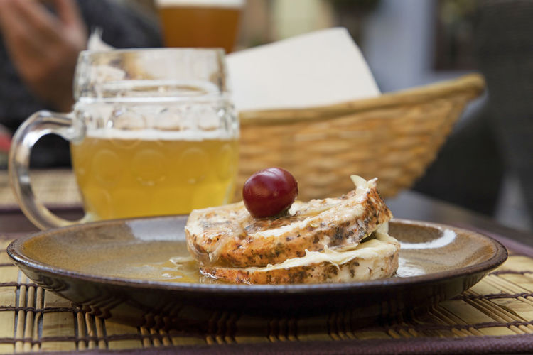 Close-up of pickled hermelin cheese served with beer on table