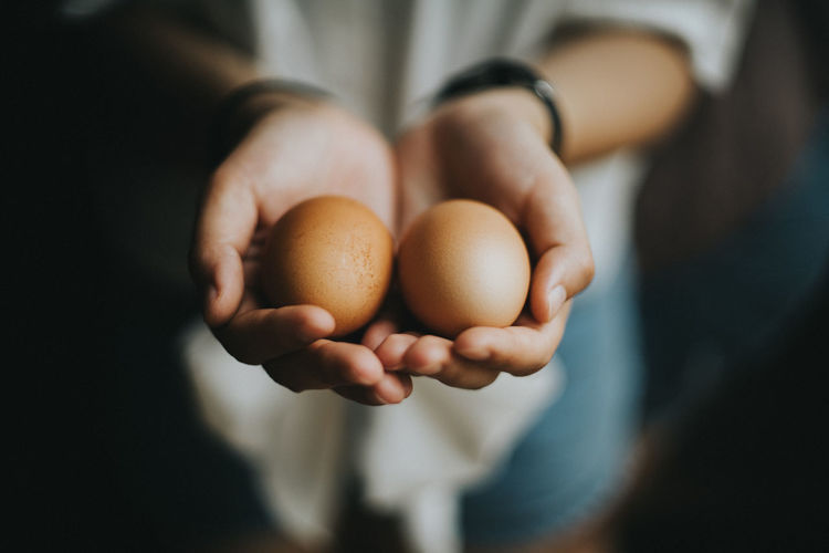 Midsection of woman holding eggs