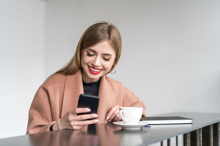 Wireless Technology Communication Technology Mobile Phone Connection Holding Portable Information Device Coffee Cup Coffee - Drink One Person Coffee Young Adult Smiling Smart Phone Telephone Pretty Girl Pretty Beautiful Smile Beautiful Woman Using Phone Front View Young Women Copy Space Lifestyle Fashion Happy Texting Mug White Background