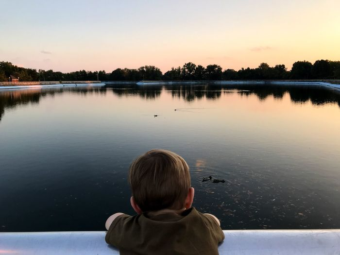 Rear view of boy in lake against sky during sunset