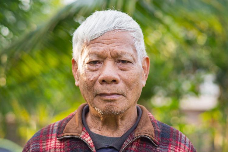 Portrait of elderly man standing in garden.