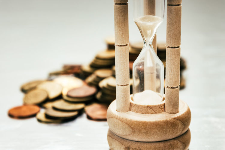 Close-up of hourglass and coins on table