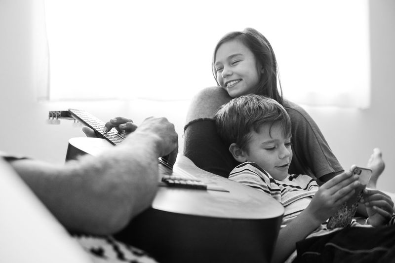 Midsection of father playing guitar while sitting with children against window at home