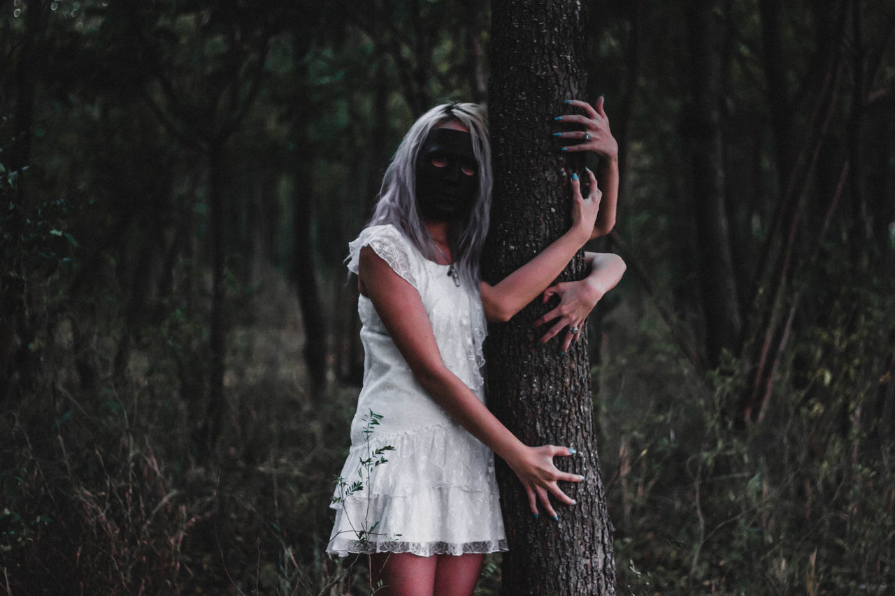 Women hugging trees in forest
