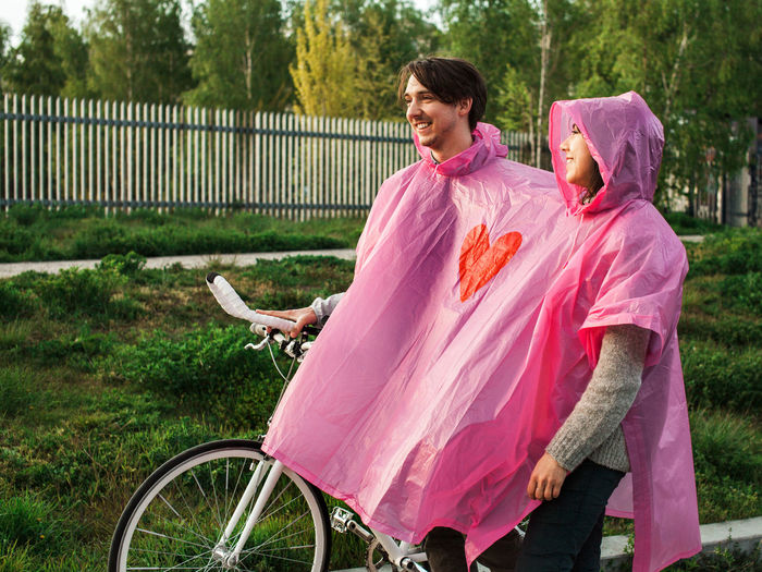 Couple wearing one piece two people rain poncho walking the bike City Couple Date Love Pink Bike Park Real People Together Two Urban Walking