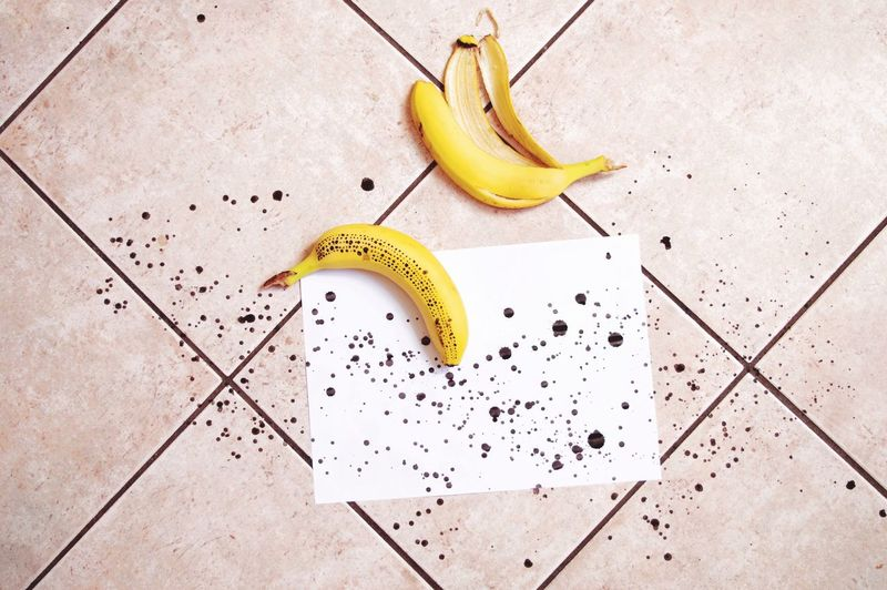High angle view of banana with ink spots and paper on tiled floor