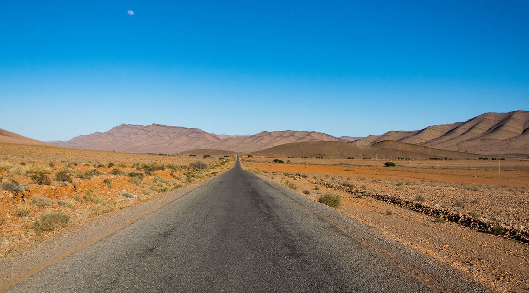 on the road from Desert The Way Forward Arid Climate Landscape Clear Sky Scenics Road Mountain Heat - Temperature Outdoors Adventure Beauty In Nature Sand Dune Nature Day No People Sky