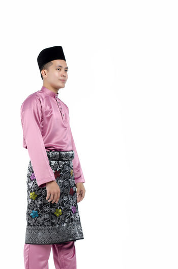 Portrait of young and handsome asian man with traditional clothing during hari raya over white background White Background Standing One Person Three Quarter Length Studio Shot Copy Space Front View Casual Clothing Indoors  Lifestyles Looking Young Adult Clothing Women Looking Away Hat Cut Out Child Contemplation