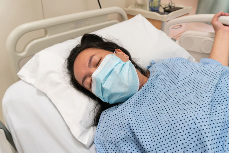 High angle view of woman wearing mask sleeping on bed in hospital