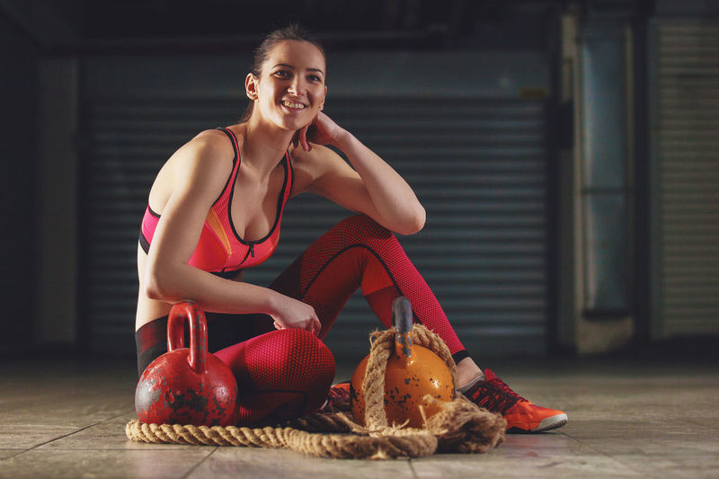 Young Woman Sitting With Kettlebells And Battle Rope In Gym