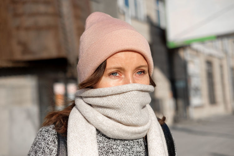 Close-up portrait of woman wearing scarf and knit hat outdoors during winter