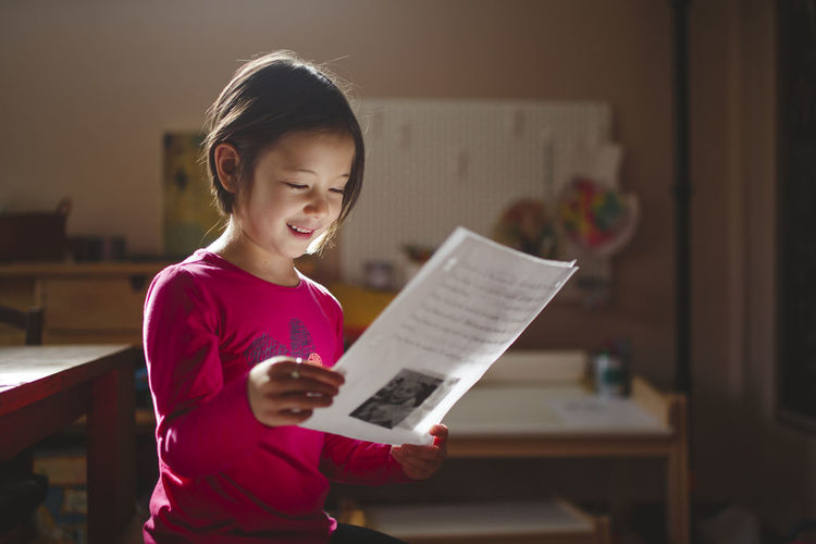 Girl holding book at home