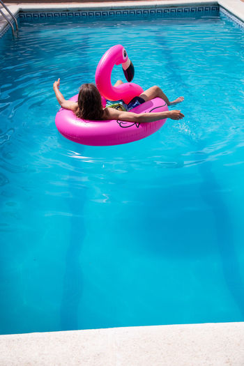 Woman relaxing in inflatable ring on swimming pool