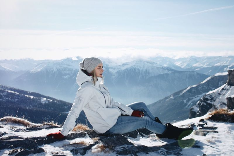 Side view of woman sitting on snowy mountain peak